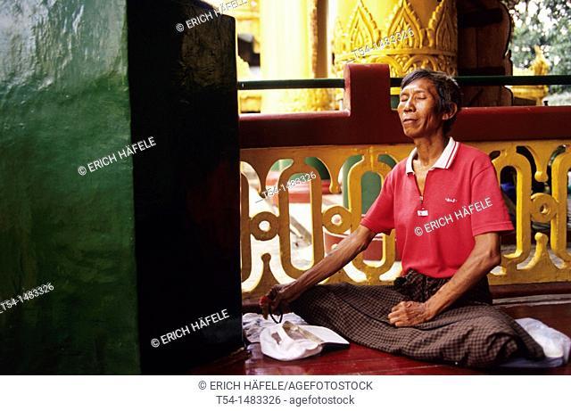 Burma pilgrim meditates in the Shwedagon Pagoda