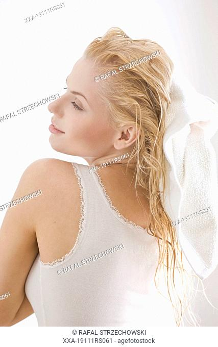 woman dries hair with towel