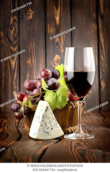 Wine glass and grapes in a basket on a wooden background