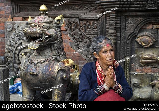 Portrait of a woman, Hindu, in front of Hindu Bairavnath temple, hands folded for the greeting Namaste, Bhaktapur, Kathmandu valley, Nepal, Asia