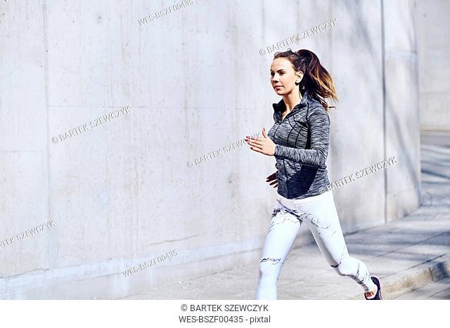 Female runner, concrete wall
