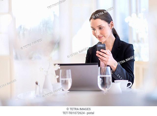 Businesswoman working on laptop in restaurant