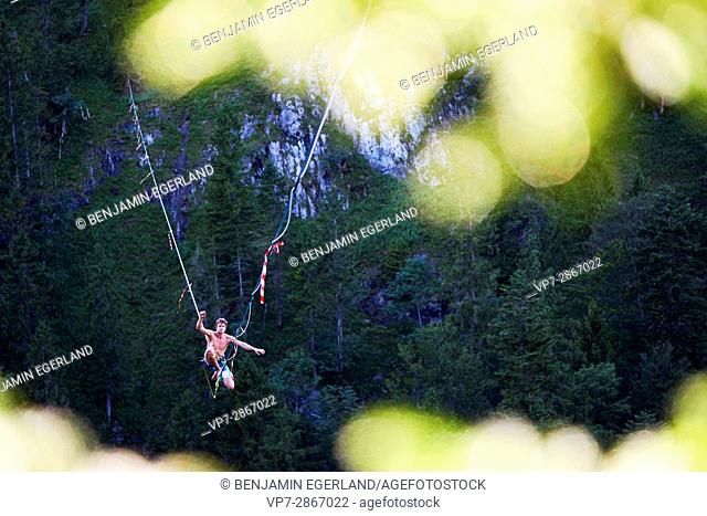 young outdoor sportsman balancing and trying to stand on highline slackline above valley in south of Germany, Bavaria, near border to Austria