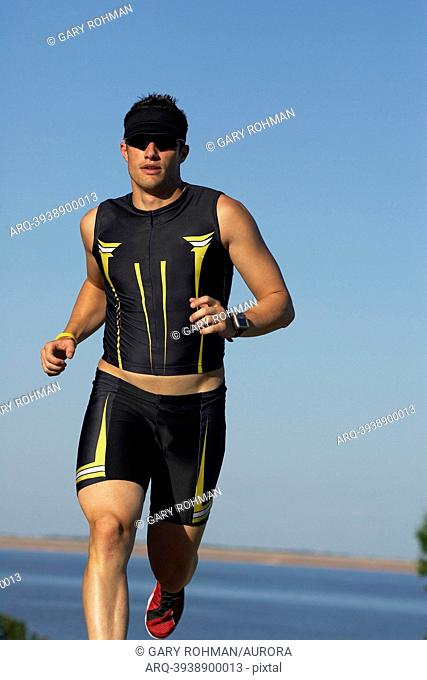A male athelete running while training for a triathlon at a lake