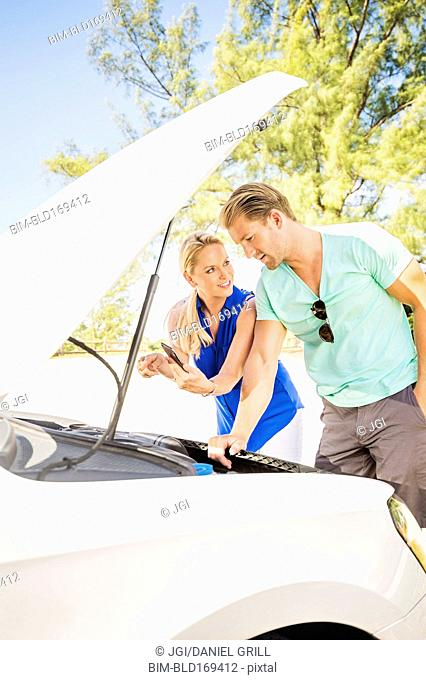 Caucasian couple examining broken down car