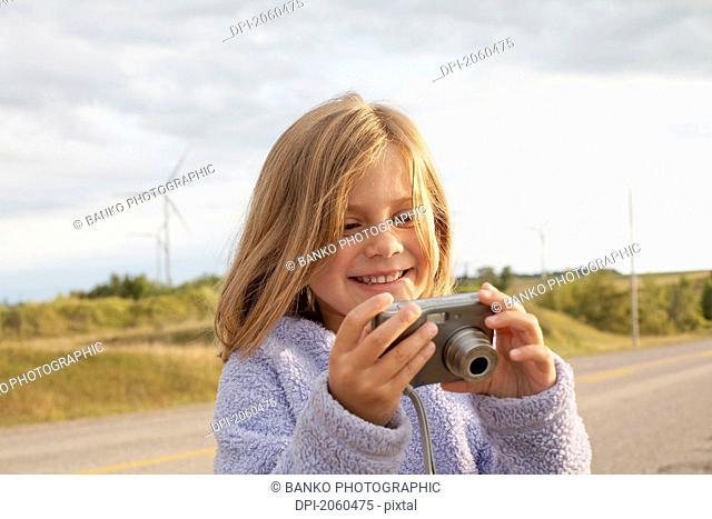 Girl Looking At Digital Camera In Front Of Wind Turbines, Tiverton, Bruce Peninsula, Ontario