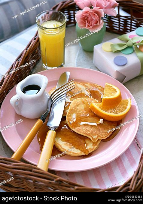 Pancakes with maple syrup and oranges for breakfast