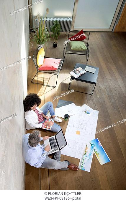 Businessman and businesswoman sitting on the floor in a loft working with laptop and documents