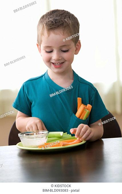 Caucasian boy eating vegetables and dip