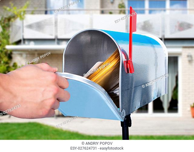 Man opening his mailbox to remove mail inside close up of his hand on the open door against a blue sky