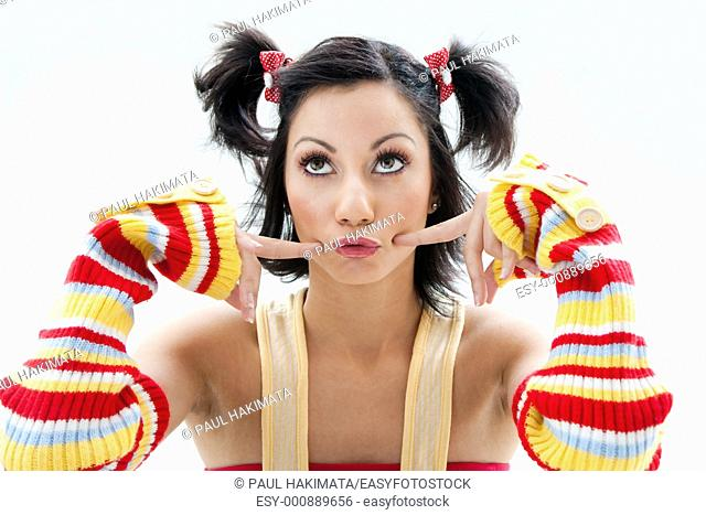 Beautiful fun latina girl with bright colored arm warmers and ponytails with red ribbons in her hair looking up, isolated