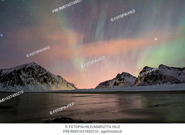 Aurora borealis at Flagstad beach, Lofoten, Nordland, Norway, March 2017, looking northeast over the Vareidsundet to Vareid with the mountains Hustinden (left)...