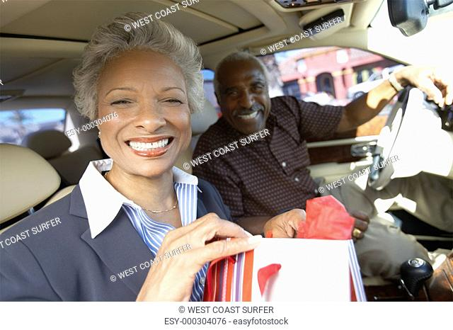 Smiling Couple sitting in car on Shopping Trip