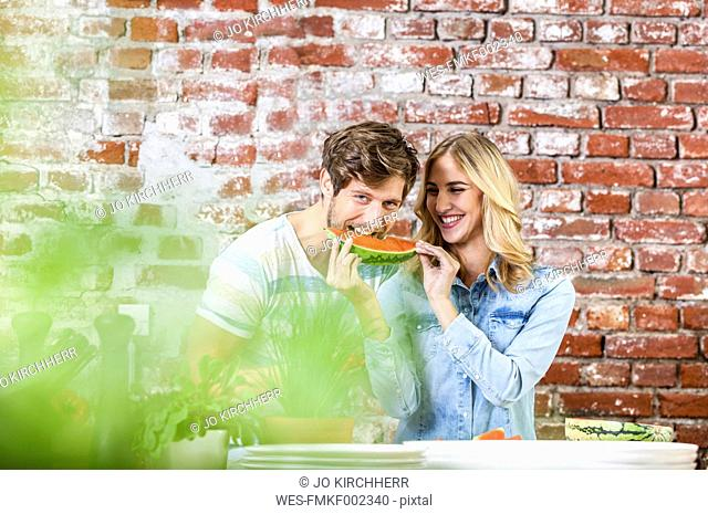 Happy young couple in kitchen eating watermelon together