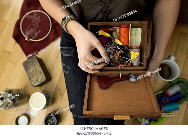 Overhead view woman looking through sewing box
