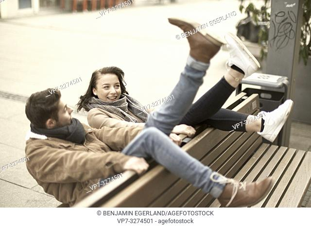young teenage couple sitting on bench the wrong way round in city, hanging out together, legs up, upside down, in Cottbus, Brandenburg, Germany