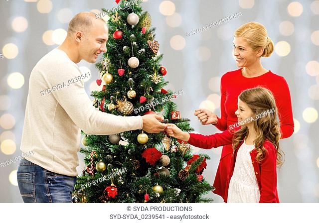mother, father and daughter at christmas tree
