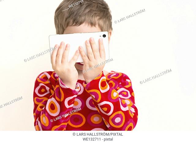 Little girl with red dress looking at smart phone