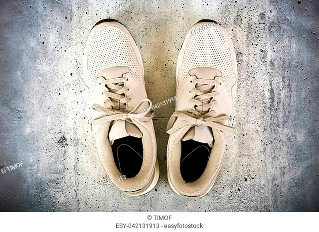 Pair of men's sports shoes on a concrete background