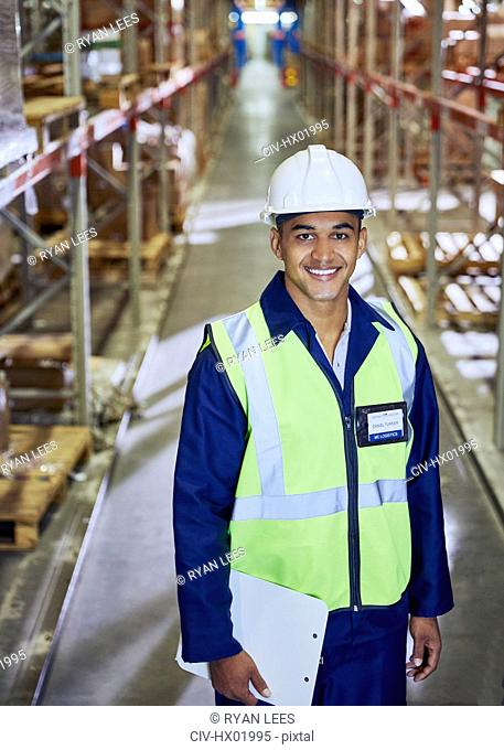 Portrait smiling worker with clipboard in distribution warehouse aisle