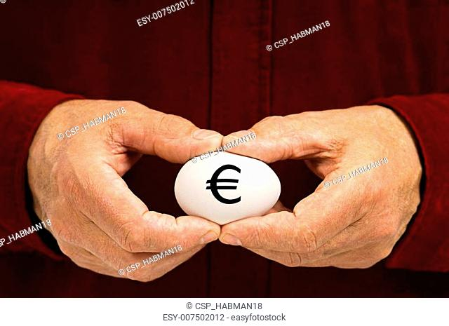 Man holds white egg with the Euro symbol written on it