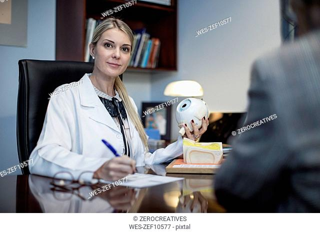 Female optometrist talking to patient, holding model of eyball
