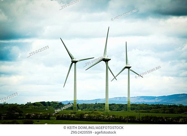 Three wind turbines in still wind on the East coast of rural Ireland near Wexford town in South eastern ireland
