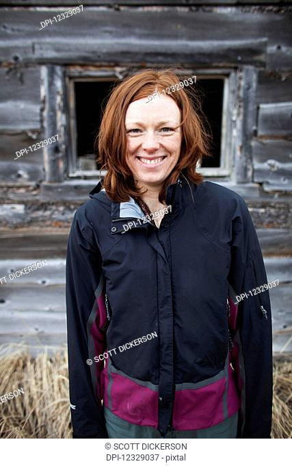 Portrait Of A Woman With Red Hair Standing And A Wooden Building In The Background; Alaska, United States Of America