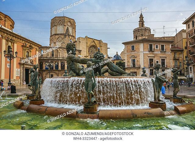 Turia fountain with the Virgen de los Desamparados Basilica and Santa Maria de Valencia Cathedral in the background . Plaza de la Virgen