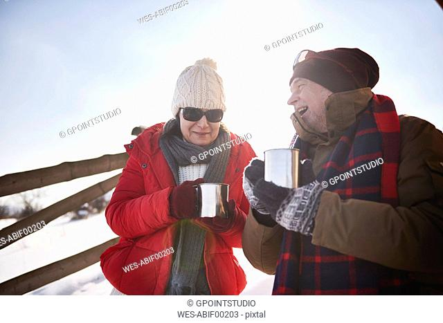 Happy mature couple with hot drinks outdoors in winter