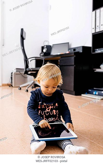 Little girl sitting on the floor at home using tablet