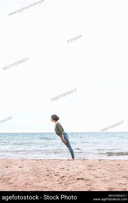 Young woman standing on the beach, tilted