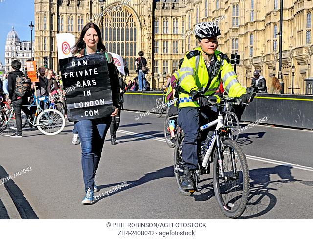 Female police officer on a bicycle at the 'Time To Act' climate march through London to Parliament for a rally, London, 7th March 2015