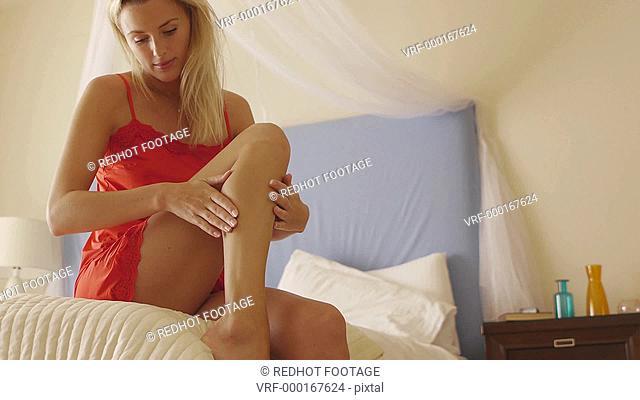 Medium shot of woman putting cream on her leg, Marbella region, Spain