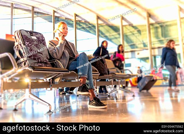 Casual blond young woman talking on cell phone while waiting to board a plane at bussy airport departure gates