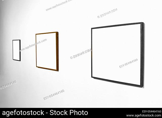 Empty blank picture wooden frame in interior on white wall