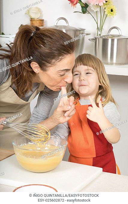 three years old child and mother sucking their fingers to taste whipped cream, together in teamwork, making and cooking a sponge cake at kitchen home