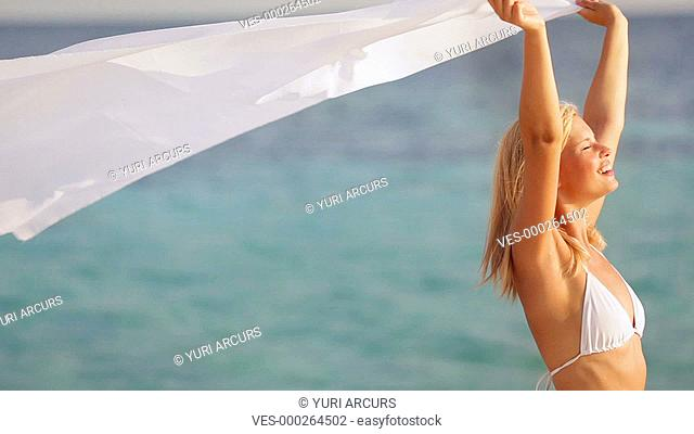 Beautiful and carefree woman holding a white sarong enjoying a beach breeze in the sun
