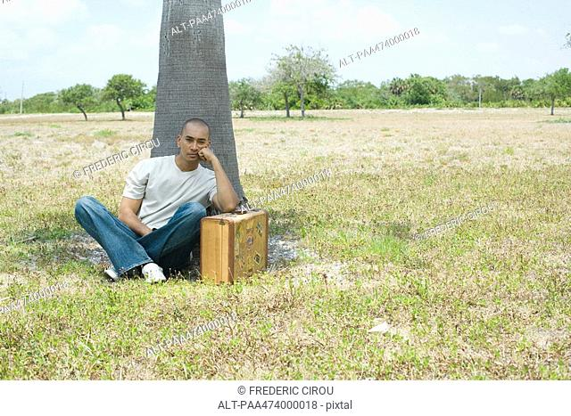 Man sitting on ground leaning against suitcase, looking at camera