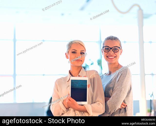 Business Women Using Digital Tablet in Busy Office