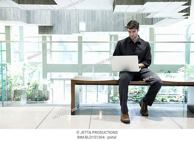 Caucasian businessman using laptop on bench
