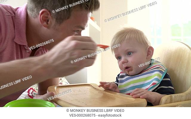 Slow motion sequence of father feeding baby son in high chair.Shot on Sony FS700 in PAL format at a frame rate of 200fps