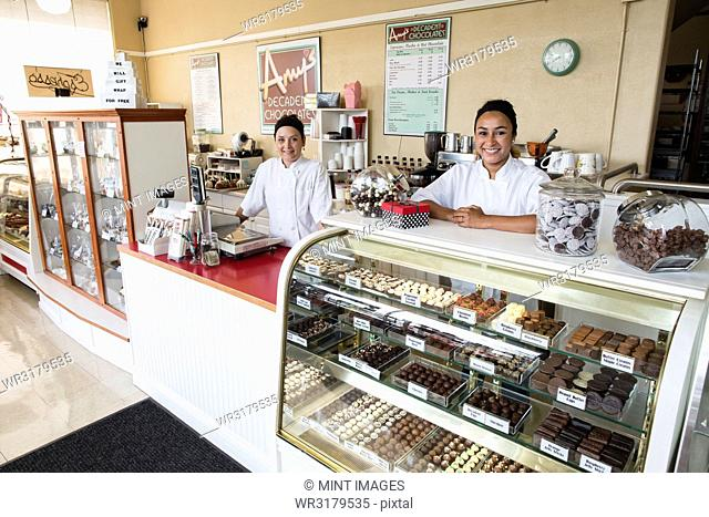 Portrait of Caucasian women co-owners of a candy shop standing behind counter
