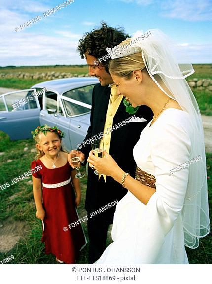 Scandinavia, Sweden, Oland, Bride and groom with flower girl, smiling