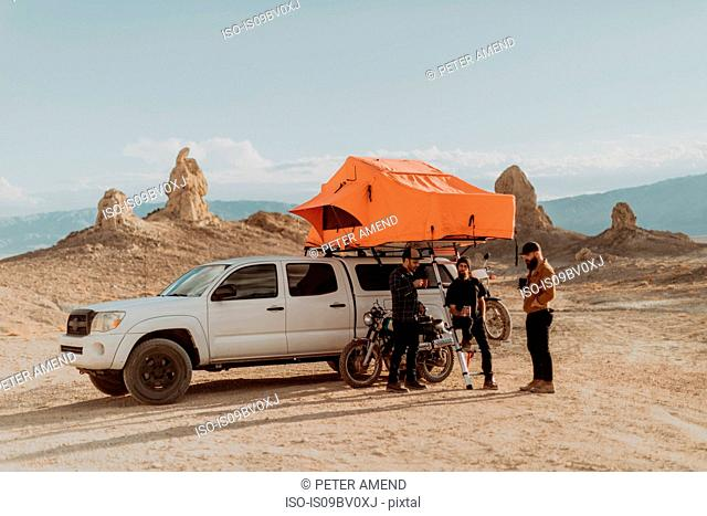 Motorcyclist friends taking break beside off road vehicle, Trona Pinnacles, California, US