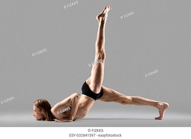 Sporty muscular young yogi man doing Eka Pada Salabhasana, one legged Locust Pose, or advanced variation of Eka Pada Ashtanga Namaskara