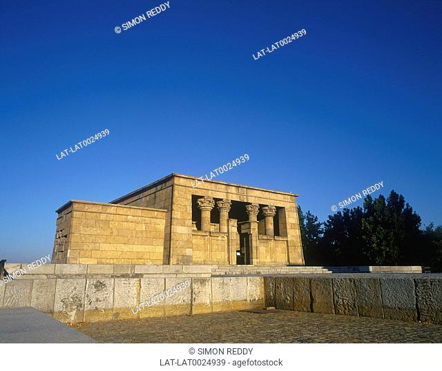 Temple de Debod. Stone building with pillars / columns. Trees behind. Blue sky