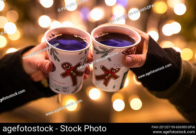 07 December 2020, Baden-Wuerttemberg, Stuttgart: Two women toast at Schlossplatz during the Corona pandemic with cups filled with mulled wine