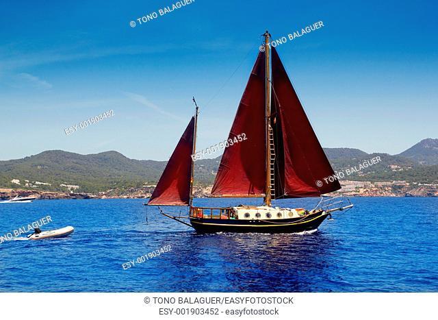 Ibiza Red sails sailboat in Sa Talaia coast of Balearic Islands