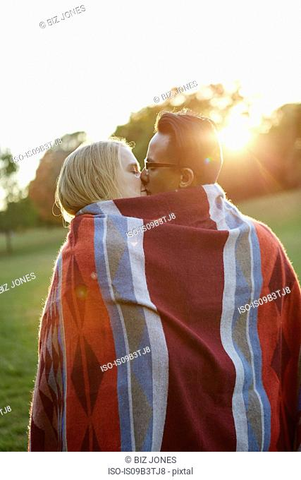 Couple wrapped in blanket, kissing in sunlit park